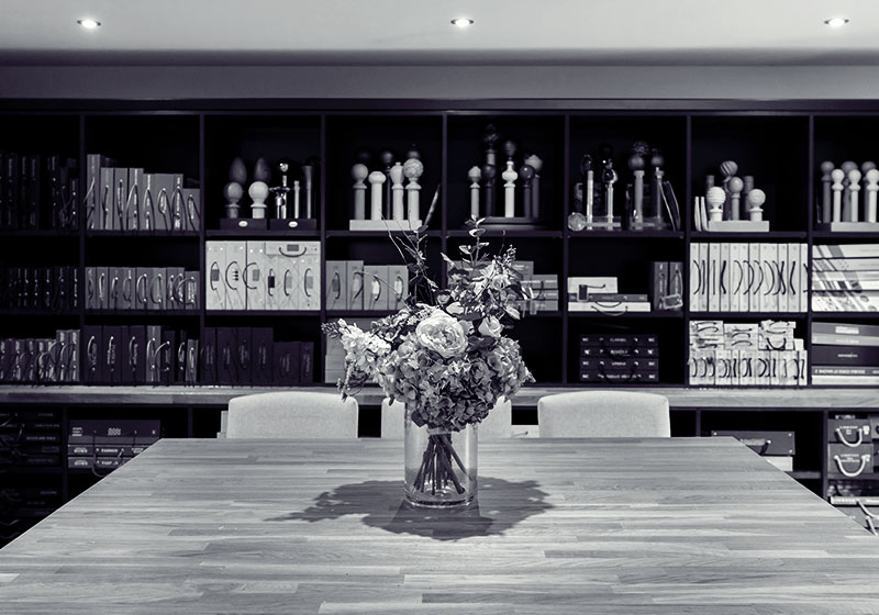 Black and white image of the studio, large island with a vase of flowers and a wall of fabric books.