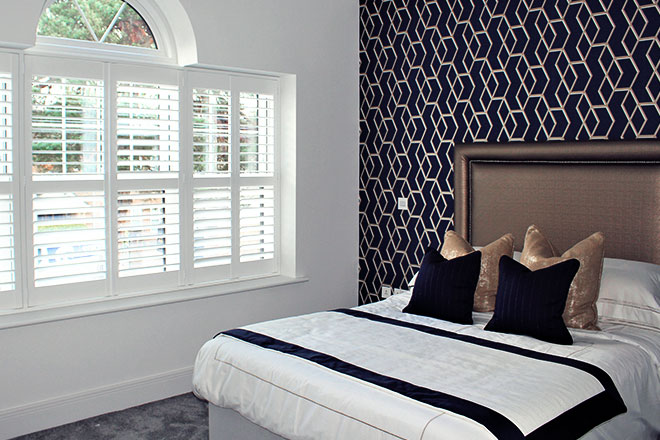 Beautiful Guest Bedroom with a navy blue and gold feature wallpaper, bespoke cushions and bed runner with white made to measure shutters at the window.