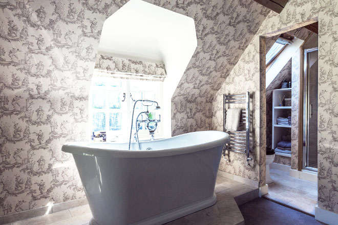 Beautiful ensuite bathroom with a free standing bath and designer fabric and wallpaper.